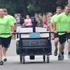 Newburyport: The Newburyport Police Department runs to the finish line in the Yankee Homecoming Lions Club Bed Race on Federal Street Thursday night. Jim Vaiknoras/staff photo