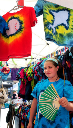 Newburyport: Samantha Simons, 10, cools off with a fan at the Market Square Craft Show. He was helping out her father, Rich, of Stone Street Tye-Dye from Walpole. Bryan Eaton/Staff Photo