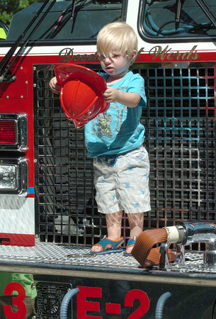 Newburyport: Rease Connatser, 2, of Salisbury kept taking his fireman's hat off as he was having his picture taken on a Newburyport fire engine at Kids Day in the Park. Bryan Eaton/Staff Photo
