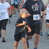 newburyport: Theo Salemi runs ahead of his dad Tom as they finish the Yankee Homecoming 5k Tuesday night. Jim Vaiknoras/staff photo