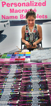 Newburyort: Som Clark, of Conn., weaves personalized macrame name bracelets at a very fast pace on State Street for the Market Square Craft Show. Bryan Eaton/Staff Photo