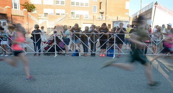 newburyport: Runner sprint by Newburyport High School as they finish the Yankee Homecoming 5k Tuesday night. Jim Vaiknoras/staff photo