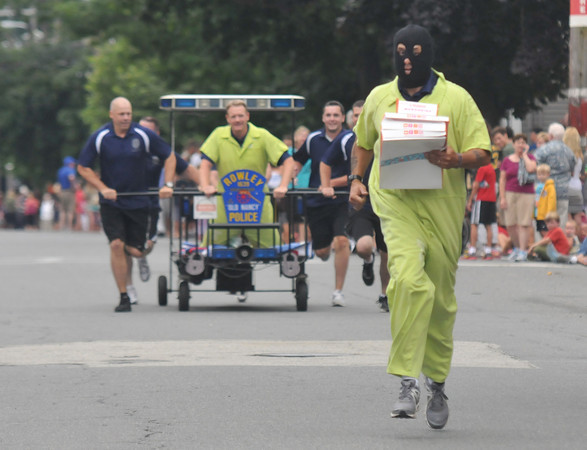 Newburyport: The Rowley Police bed chases a doughnut-stealing crook as it heads to the finish line in the Yankee Homecoming Lions Club Bed Race on Federal Street Thursday night. Jim Vaiknoras/staff photo