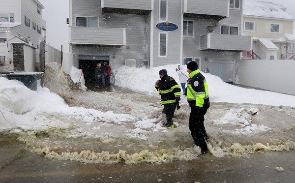 Salisbury: People who were shoveling snow and slush at Oceancrest Condominiums at Salisbury Beach take cover as water rushes to the side of the structure. Bryan Eaton/Staff Photo