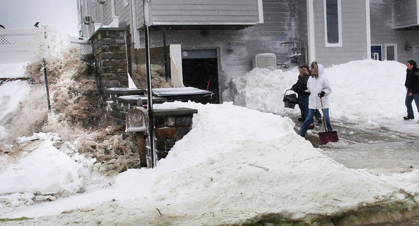 Salisbury: People who were shoveling snow and slush at Oceancrest Condominiums at Salisbury Beach are startled as water rushes to the side of the structure around high tide Saturday. Bryan Eaton/Staff Photo