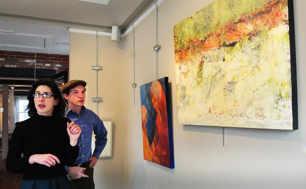Newburyport: Judges Diana Tuite, left, and Lucas Spivey look over the entries for the Newburyport Art Association's Winter Show. Bryan Eaton/Staff Photo