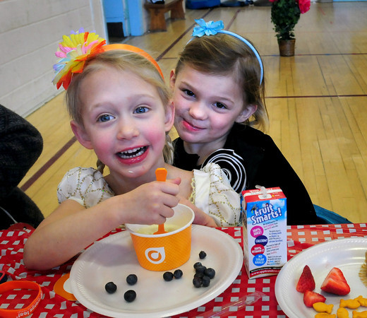 Newburyport: Preschoolers Lainey Pare, left, and Samantha Morris, both 4, enjoy their frozen yogurt provided by Orange Leaf on Thursday morning. THe two were at the Valentine Brunch as the Brown School in Newburyport also attended by their parents. Bryan Eaton/Staff Photo