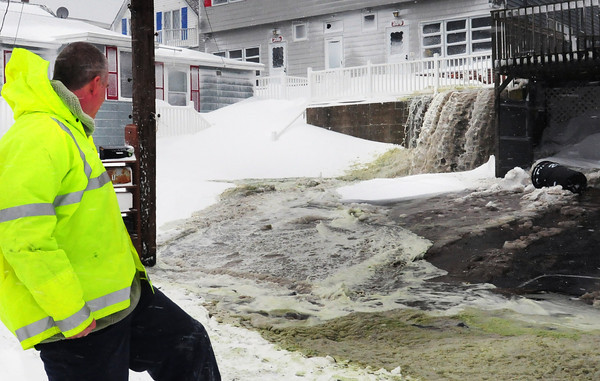 Salisbury: Stone Mickelson watches ocean water cascade next to his home at Salisbury on North End Boulevard just before high tide Saturday. Several people near him were evacuated and he was unsure if he was going to be as well. Bryan Eaton/Staff Photo