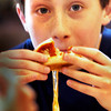 Newburyport: Children at Newburyport's Kelley School Drop-In Center got lessons in making pizza, though they weren't tossing dough in the air, just putting tomato sauce and mozzarella on cut bagels and baking them. Chris Connor, 11, seemed to have gotten a little more of the cheese than he can handle. Bryan Eaton/Staff Photo