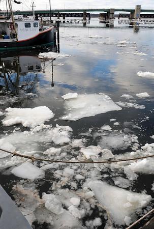 Newburyport: Ice breaking up from warmer temperatures up the Merrimack River float down past Newburyport's waterfront. Bryan Eaton/Staff Photo