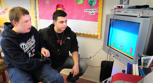 Newburyport: Cameron Toy, left, a post graduate at Newburyport High, and Andreas Asprogiannis designed a joystick in their Technology Class so that Cameron could play video games using his left hand and feet that push two pads on the floor. Bryan Eaton/Staff Photo
