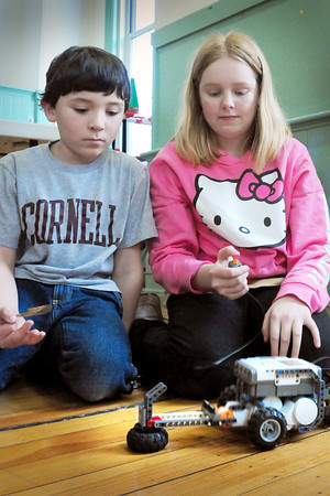 """Newburyport: Garrett Campbell, 8, left, and Devan Latham, 11, try out their robotic """"hammer car"""" which they made from Legos at the Kelley School Youth Center. Kevin Husson, who has been teaching the classes for Lego building this week, owns Seacoast Technology Workshop which works with youngsters during summer and winter school breaks. Bryan Eaton/Staff Photo"""