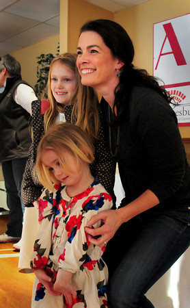 Bella Freeman, 9, and her shy sister Madelaine, 3, of Amesbury, pose with legendary skater Nancy Kerrigan at the Amesbury Sports Park on Thursday sponsored by the Amesbury Chamber of Commerce and Industrial Foundation and Shaheen Bros., Inc. A small skating rink was built for Kerrigan to perform, but warm weather washed those plans away. Bryan Eaton/Staff Photo