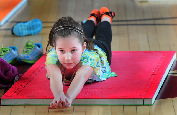 Newburyport: Ella Rogers, 8, balances on her tummy while outstretching her arms and legs at the Bresnahan School. Children in Jesse Craddock's physical education class were learning basic static balancing skills. Bryan Eaton/Staff Photo