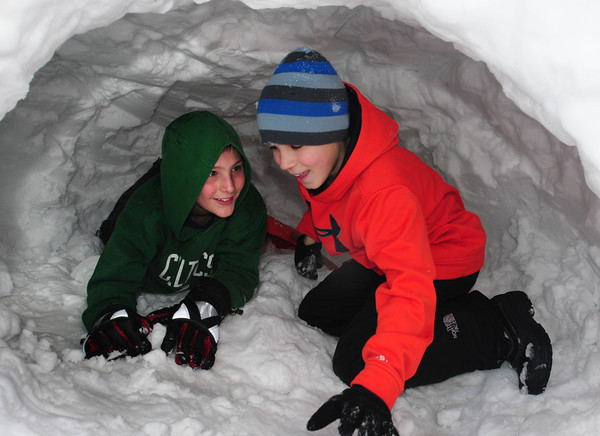 Newburyport: Noah van Schalkwyk, 13, left, and Ethan Coir, 12, squeeze into their Quinzhee awaiting others from their team to see how many they can fit it. Bryan Eaton/Staff Photo