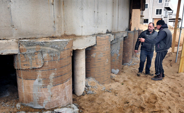 Newbury: Tom Nee, right, with friend Tom Eramo, has constructed huge cement and rebar columns at his threatened home on Plum Island. The columns go down 16 feet from the top to the base buried in the sand. Bryan Eaton/Staff Photo