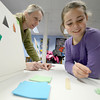 Amesbury: Libby Waterman, 8, watches as Origami teacher Laura Geggis<br /> flips a Origami frog at a program at the Amesbury Library Thursday. along with frogs , kids made whales , balloons and cicada bugs . Jim Vaiknoras/staff photo