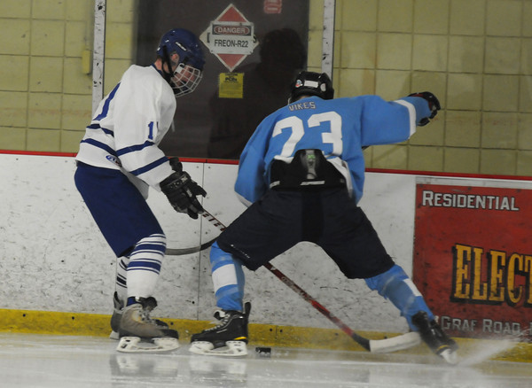 Newburyport: Triton's Shea Capolupo and Danvers player Jay Calcagno fight for the puck during their game at the Graf Rink Friday. Jim Vaiknoras/staff photo