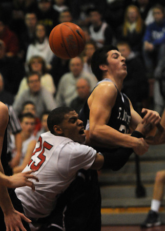 Lawrence:Central's Joel Berroa is fouled by  St John's Jake Burrduring thier game at Central Catholic Sunday night. JIm Vaiknoras/staff photo