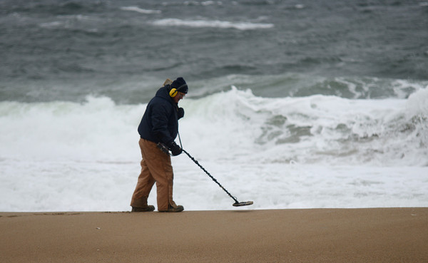 Salisbury: Dana King of Thorton NH searches Salisbury Beach with a metal detector Friday morning, he is hoping the blizzard uncovers some interesting objects. Jim Vaiknoras/staff photo