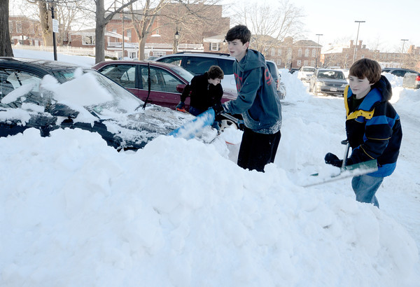 Newburyport: Brothers Colin, John , and Chris Brennan of Newbury committ random acts of shoveling as they clear snow from cars in the central parking lot in Newburyport Sunday morning. After church they started shoveling out some of their fellow parishiners and just kept going. Jim Vaiknoras/staff photo