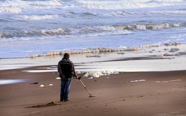 salisbury: A man with a metal detector combs Salisbury Beach for valuables churned up by this past weekend's storm. JIm Vaiknoras/staff photo