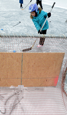 West Newbury: Macy Antonopoulas, 6, take a turn shooting a puck through a target at the Mill Pond Winter Carnival Sunday in West Newbury. Jim Vaiknoras/staff photo