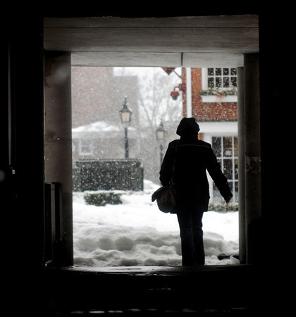 Newburyport: A woman walks through the tunnel connecting State Street and Inn Street in Newburyport as snow falls Sunday afternoon. Jim Vaiknoras/staff photo