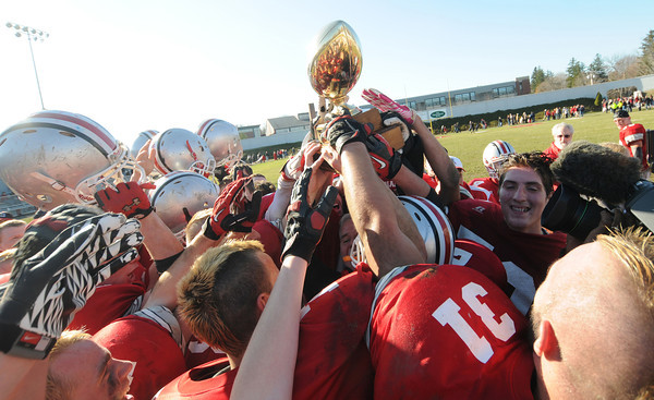 Amesbury: Amesbury football player hold up the trophy after their 13-10 victory against Newburyport Thursday. JIm Vaiknoras/staff photo