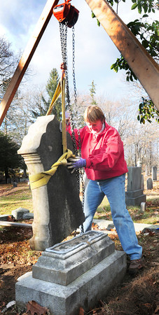 Newburyport: Ghlee Woodworth lowers one of several gravestones back onto the which which she spread epoxy to keep in place. A couple hundred stones are behing reattached to the base from which they fallen either by natural means or vandalism. Bryan Eaton/Staff Photo