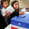 Newbury: First-graders Carson Irving, left, and  Hannah Papoulias cast their ballots Friday in a mock election at Newbury Elementary School. The youngsters who won't really vote for another 12 years were voting the in the presidential race. Bryan Eaton/Staff Photo