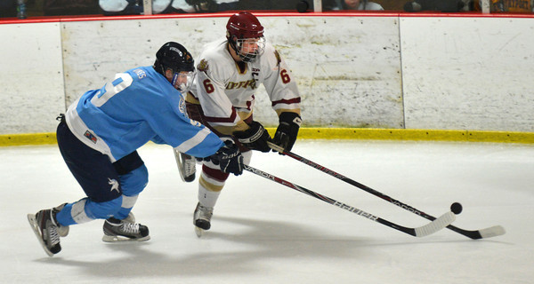 newburyport: Newburyport's Connor Wile reaches for the puck with Triton's Jacob Wood during their game at the Graf Rink in Newburyport saturday. Jim Vaiknoras/staff photo