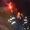 Newbury: Bethany Groff of the Spencer Pierce Little Farm gets ready , along with Newbury Firefighter, to light <br /> the pile of trees at the Tendercrop Farm growing fields for the annual Christmas Tree bonfire Saturday night. Jim Vaiknoras/staff photo
