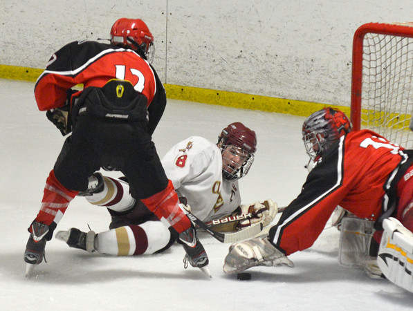 Newburyport: Amesbury's Evan King covers up a shot by Newburyport's Tyler Cusack during their game at the Graf Rink in Newburyport Saturday night. Jim VAiknoras/staff photo