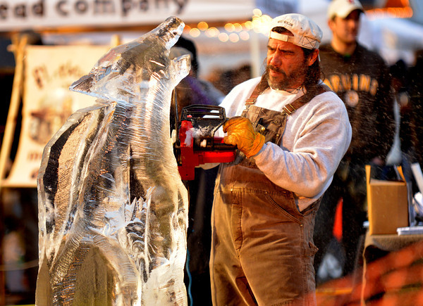 Newbury: Fred Stanton carves a wolf out of ice at the annual Christmas Tree bonfire Saturday night in Newbury. Jim Vaiknoras/staff photo