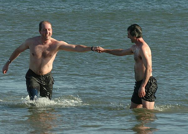 Salisbury: Carl Clarizia fist bumps Nick Vantzlfde as they swim at Salisbury Beach after running the Winner's Circle New Year's Classic Tuesday. Jim Vaiknoras/staff photo