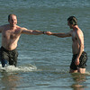 Salisbury: Carl Clarizia fist bumps Nick Vantzlfde as they swim at Salisbury Beach after running the Winner's Circle New Year's Classic Tuesday. Jim Vaiknoras/staff photo