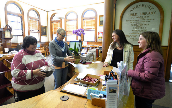 Amesbury: Dorothy McGrath and Danielle Levy give muffins and a plant to Margie Walker and Julie Lemieux at the Amesbury Library Saturday. Jim Vaiknoras/staff photo