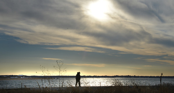 salisbury: A man walks along the seawall in Salisbury in the late afternoon sun Saturday . Jim Vaiknoras/staff photo