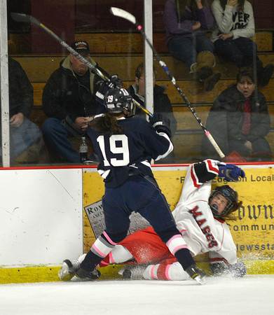 Newburyport: Masco player Alexandra Casale of North Andover is  checked by a Medford player during their game at the Graf Rink in Newburyport Wednesday night. Jim Vaiknoras/staff photo