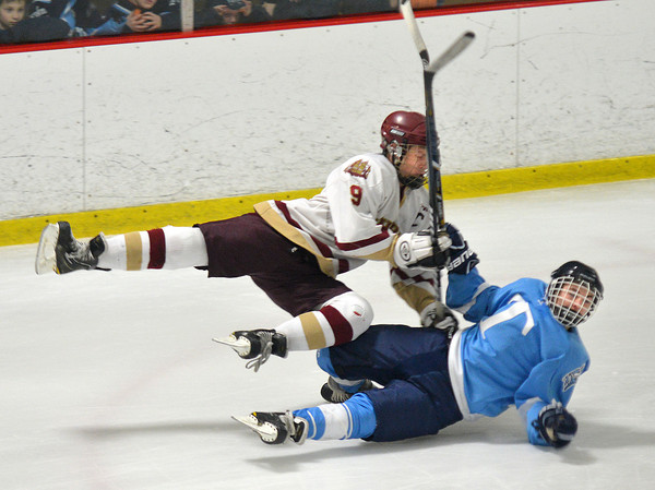 newburyport: Newburyport's Nicholas Mombello checks Triton's Shea Capolupo during their game at the Graf Rink in Newburyport saturday. Jim Vaiknoras/staff photo