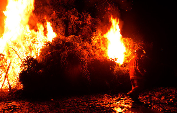 Newbury: A firefighter walks through thick mud while lighting the pile of trees at the Tendercrop Farm growing fields for the annual Christmas Tree bonfire Saturday night. Jim Vaiknoras/staff photo
