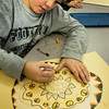 Newbury: Charlie Grossman, 8, works on his cat mat in art class with crayon where they were learning about concentric ovals and circles. The Newbury Elementary School youngster, who doesn't have a cat but likes them, will later create a watercolor of a cat on the mat. Bryan Eaton/Staff Photo