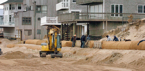 Newbury: Workers install giant sandbags at homes along Annapolis Way on Plum Island that have been threated by erosion. Bryan Eaton/Staff Photo