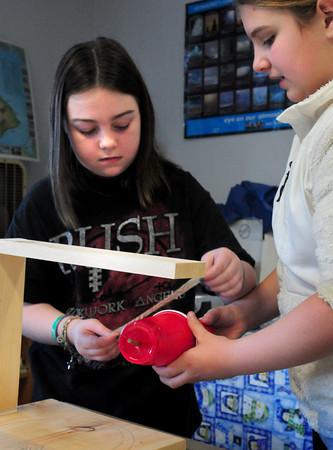 """Amesbury: Amesbury Middle School sixth-graders Tori Demetrio, left, and Anna Iacobucci, both 11, work on their seismograph """"Shake o' Make"""" which their team designed. The students were helped by Stacy Moulis, a seismologist at the Weston Observatory on Thursday. Bryan Eaton/Staff Photo"""