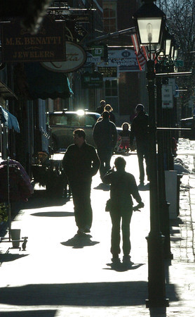 Newburyport: Afternoon sun reflects off the sidewalk on State Street in Newburyport yesterday silhouetting pedestrians. While the sun did shine bright, the wind kept things pretty cool. Bryan Eaton/Staff Photo
