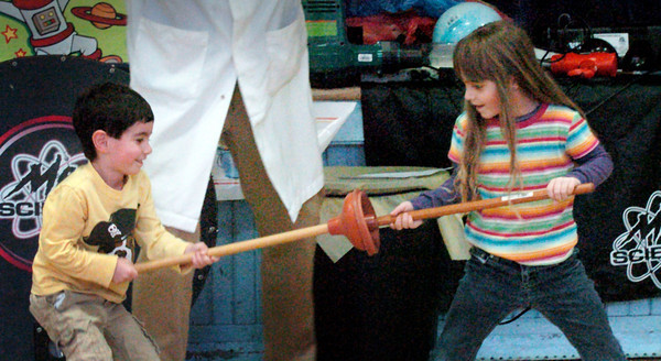 Newburyport: Jake Blinderman, 4, left and Katelyn Holleran, 5, try to pull apart two toilet plungers at the Brown School on Monday. They were at a science presentation teaching children about air science, including the lack of air here between the plungers: a vacuum. Bryan Eaton/Staff Photo