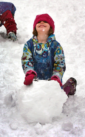 Newburyport: Brooke Lawton, 5, rolls up some snow for a snowman Wednesday at the Inn Street Playground in Newburyport. Children haven't had much of the white stuff to play in to she and her class from the Newburyport Montessori School took to the outside for playtime. Bryan Eaton/Staff Photo