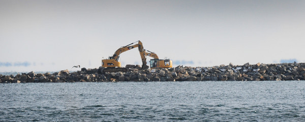 Newburyport: Heavy equipment working on the repair of the south jetties of the mouth of the Merrimack River can be seen from Salisbury Beach State Reservation. Some of the large planks laid to allow easy access of the equipment was washed away by last week's storm. Bryan Eaton/Staff Photo