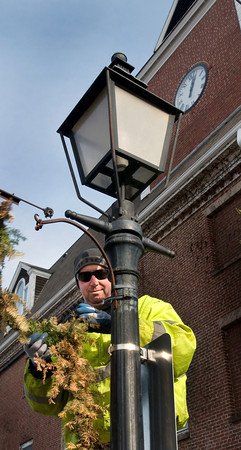 Newburyport: Dan Keefe from the Newburyport Department of Public Services takes garland down from the lampposts in downtown Newburyport on Tuesday afternoon. Earlier in the day they took down the Christmas tree in Market Square and sent it through the chipper. Bryan Eaton/Staff Photo